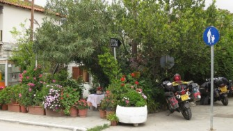 Cottage hidden behind bushes in the middle of tourist town. The owner was sitting behind the geraniums, watching the world go by. He did peek around the corner to investigate our bikes though ;)