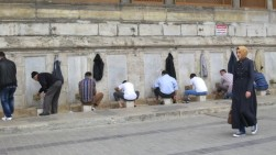 Men washing their feet before going inside to pray