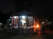 an outside shrine with lit fire and people praying as they circle around the deieties inside the fence